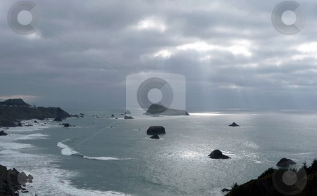 Light from the heavens stock photo, Sunlight streams through heavy clouds and lights up the surface of the ocean by Jill Reid