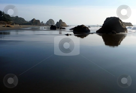 Water and sky reflections on beach stock photo, The sky reflects its colors on the water and sand on a rocky beach in Oregon by Jill Reid