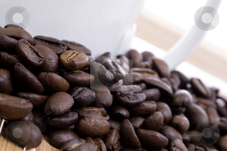 Coffee beans and cup stock photo, Coffee beans and cup on wooden table by iodrakon