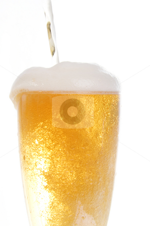 Pooring beer onto glass stock photo, Beer being poored onto tall glass over white background by iodrakon