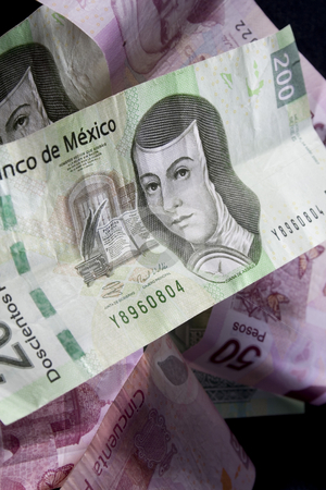 Mexican Money stock photo, Close up shot of mexican currency over black background by iodrakon