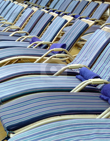 Pool deck chairs on a cruise ship stock photo, A row of blue striped lounge chairs around a cruise ship pool by Jill Reid