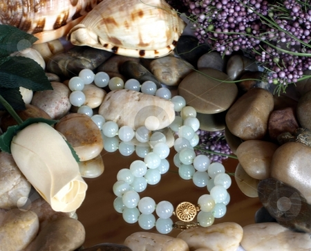 Green bead necklace with gold claps and zen pebbles stock photo, Collection of green bead necklace, shells, spa items by Jill Reid