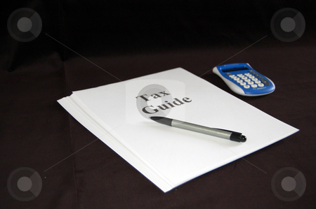 Tax Guide Document with Pen and Calculator stock photo, Shot of a tax guide document with a pen and a calculator sitting next to document. by Valerie Garner