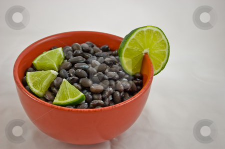 Red Bowl of Black Beans and Lime stock photo, Closeup photo of a red bowl of cooked black beans and lime as garnish, isolated on a white background. by Valerie Garner