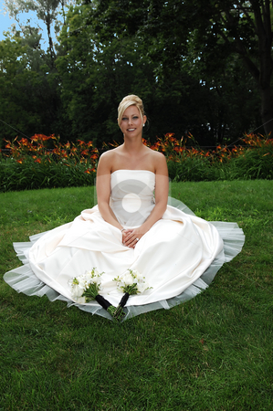 The bride alone. stock photo, The newly wed bride sitting on the grass in the park for a photo shoot. by Horst Petzold
