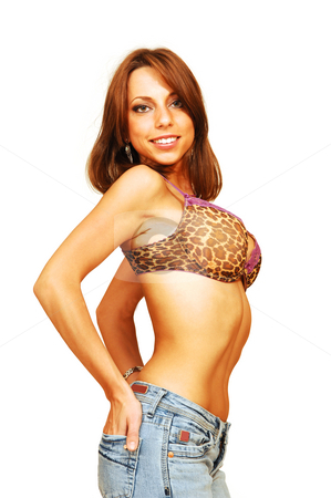 Standing woman in bra and jeans. stock photo, An very fit woman in a nice bra and jeans standing in an   studio for white background and shooing her great figure. by Horst Petzold