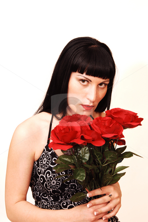 Young serious looking girl with roses. stock photo, An young pretty girl in a black and white dress and a bunch of red roses standing in an studio for white background. by Horst Petzold