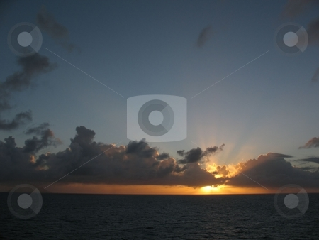 Sunset in the Caribbean stock photo, This was taken just off  Marinique in the eastern Caribbean in January with rain clouds moving toward the island. by Ray Carpenter