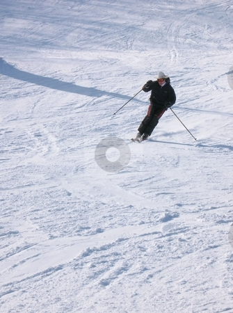 A Happy Skier stock photo, A skier coming down from the mountain, turning into a traverse to change direction, throwing up some snow. by Ray Carpenter