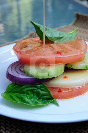 Vegetable And Cheese Salad stock photo, Italian dressing pouring over  the top of tomatoes, cucumber, red onion and mozzarella cheese slices topped with basil. by Lynn Bendickson