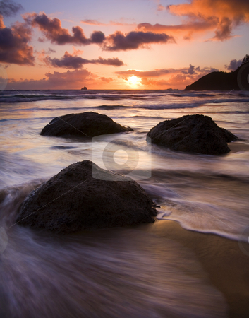 Three Surrounded stock photo, Three large boulders surrounded by the tides at sunset on Ecola Beach by Mike Dawson