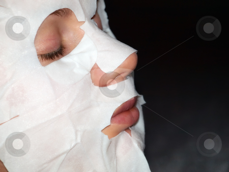 Cosmetic mask stock photo, Girls face hidden beneath the cosmetic masks during cosmetic treatment. by Sinisa Botas