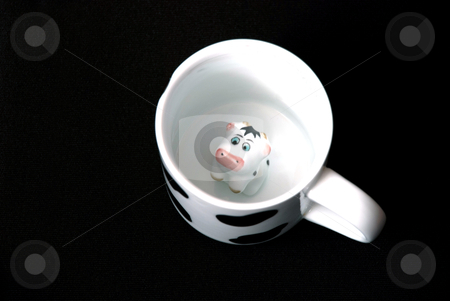 A milk mug with cow stock photo, A milk mug with cow inside on a black background by Alexey Rumyantsev
