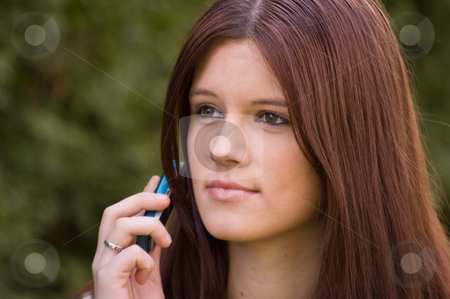 Attractive Young Woman on Her Cell Phone stock photo, Attractive young woman Caucasian is on her teal colored cell phone that's a modern update to date version of this technology. by Valerie Garner