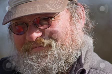 Closeup Facial Shot of Middle Aged Scruffy Man stock photo, This closeup shot of a Caucasian middle aged man with his full graying beard, is a rough, scruffy rugged looking male. by Valerie Garner