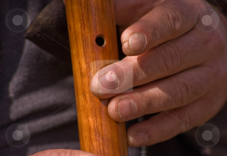 Closeup of Rough Worker Hands Playing Wooden Flute stock photo, A closeup shot of a man's rough labor working hands, playing a wooden Native American flute. by Valerie Garner