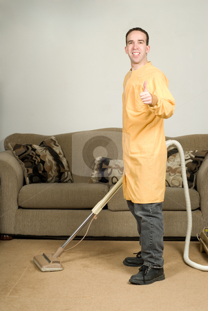 Daily Chores stock photo, A happy worker cleaning the carpets and giving the camera a thumbs up by Richard Nelson