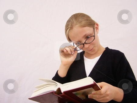 Girl with glasses reading book stock photo,  by Gregory Dean