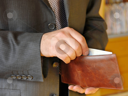Businessman with wallet stock photo, Businessman hand holding a opened leather wallet by Julija Sapic