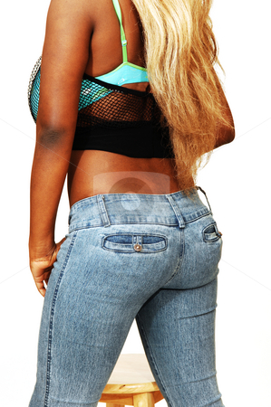 Young Jamaican girl. stock photo, An busty young Jamaican girl in jeans with long blond hair shooing her back and nice butt, standing in a studio for white background. by Horst Petzold