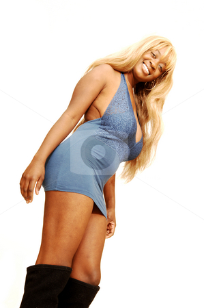 Standing blond woman in short blue dress. stock photo, An friendly blond girl in an very short blue dress standing in an studio with  long black boots for white background. by Horst Petzold