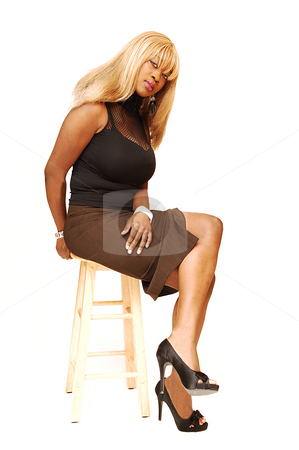 Young Jamaican girl. stock photo, An busty young Jamaican girl in a black top and brown skirt, long blond hair  sitting on an bar chair in the studio for white background. by Horst Petzold
