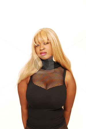 Young Jamaican girl  stock photo, An busty young Jamaican girl in a black top, long blond hair  standing in an studio for white background. by Horst Petzold
