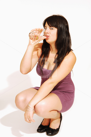 Hocking woman in pink dress.  stock photo, An friendly girl in an short pink dress hocking in an studio  for white background and drinking a glass of water. by Horst Petzold