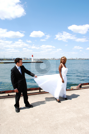 Young married couple. stock photo, An young married couple on a photo shoot at the Hamilton harbor at the light house and the lake Ontario in the background. by Horst Petzold
