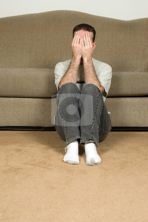 Depressed Man stock photo, A depressed man covering his face and sitting on the floor near the sofa by Richard Nelson