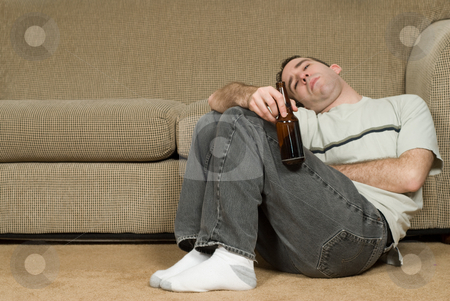 Alcoholic stock photo, A young alcoholic drunk on the floor inside a house by Richard Nelson