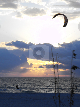 Kite boarding stock photo, A kite boarder rides the late afternoon wind along the Gulf Coast by St. Pete's Beach in Florida on a winter day. by Dennis Thomsen