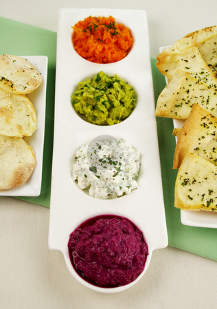 Assorted Dips stock photo, Assorted dips of beetroot, carrot, cottage cheese and herbs, pea and basil with pita crisps. by Brett Mulcahy