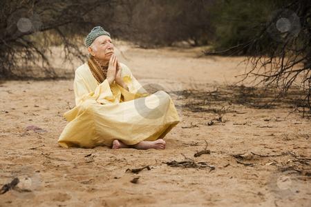 Guru in the desert stock photo, Wise man praying and meditating in the desert by Scott Griessel
