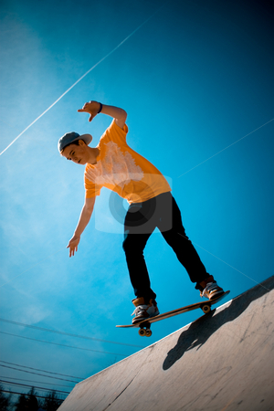 Cool Skateboarder stock photo, A young man skateboarding down a ramp at the skate park. by Todd Arena