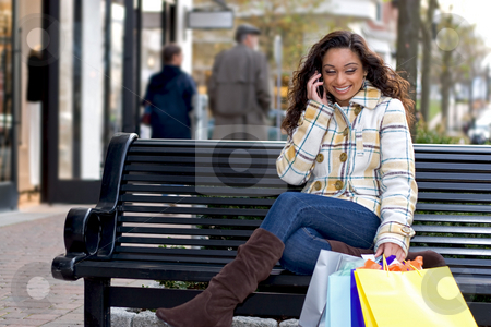 Cell Phone Break stock photo, An attractive girl talking on her cell phone while out shopping in the city. by Todd Arena
