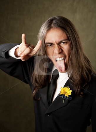 Handsome man in formalwear sticking oput his tongue stock photo, Handsome man with tongue out making bull horns gesture in formal jacket and boutonniere by Scott Griessel