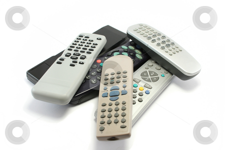 Pile of Remote Controllers stock photo, Various TV and video remote controls collecting dust around the house by Helen Shorey