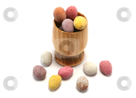 Easter Eggcup from above stock photo, Small wooden eggcup filled with candy coated chocolate Easter Eggs by Helen Shorey