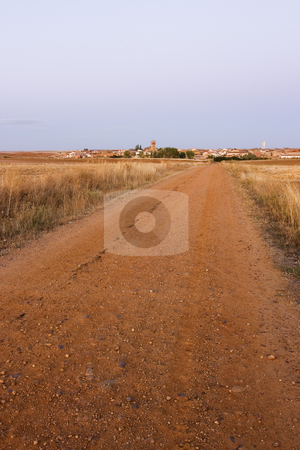 Village rural road stock photo, A rural road and a village at the background by Ivan Montero