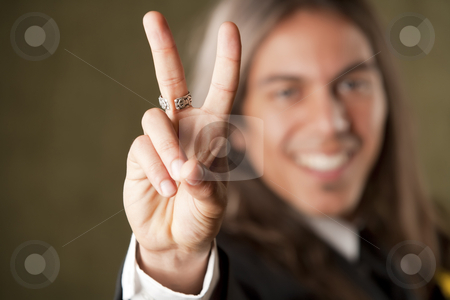 Handsome man in formalwear making a peace sign stock photo, Handsome man in formal jacket with boutonniere making peace sign by Scott Griessel