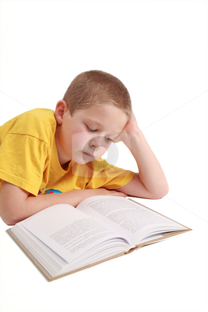 Young boy lying down stock photo, Young boy is reading the book - on white background by Tom P.