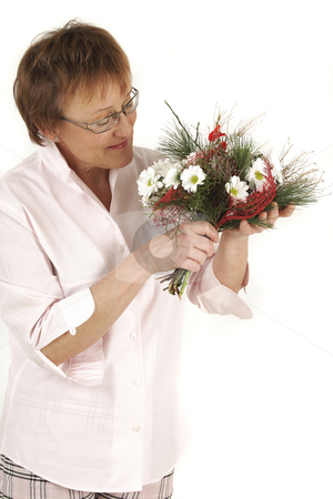 Smelling stock photo, Elderly woman is smelling to flowers by Tom P.