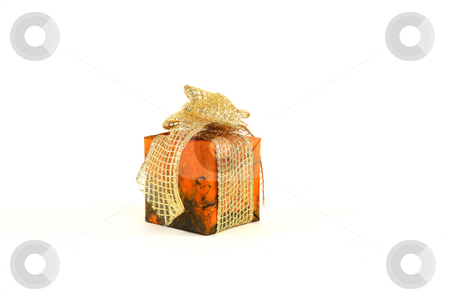Christmas present stock photo, Small christmas present in orange paper with golden tie by Tom P.