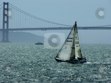 Taking the wind stock photo, A sailboat, backlit by the afternoon sun, catches the wind with San Francisco's Golden Gate Bridge as a backdrop. by Dennis Thomsen