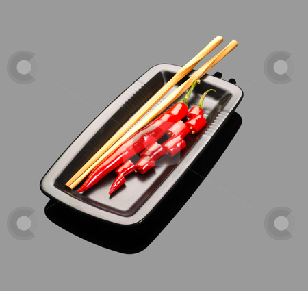 Red chili peppers stock photo, Fresh red chili peppers on a plate with chopstikcs over grey reflective surface by Francesco Perre