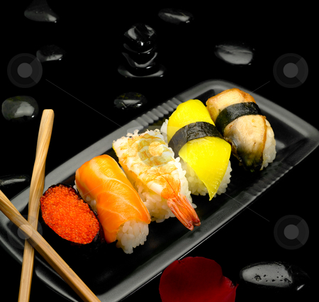 Assorted sushi plate stock photo, Assorted sushi plate on black pebbles over black background by Francesco Perre