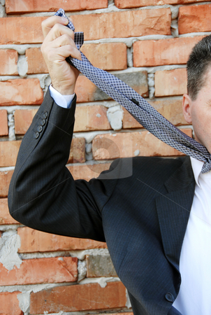 Hopeless situation stock photo, Businessman smothering himself with necktie by brick wall by Julija Sapic