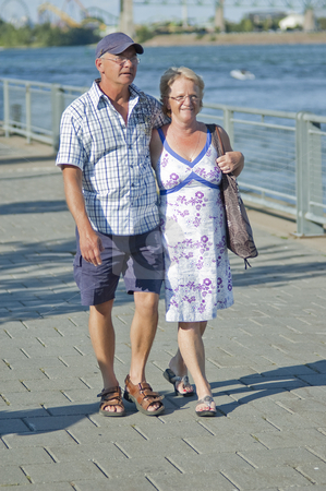 Aged couple stock photo, Aged loving couple walking and holding each other by Vlad Podkhlebnik